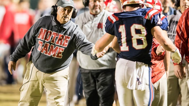 Notre Dame head coach Lewis Cook congratulates Hayden Bourgeois  (18) after he scores another Pios touchdown as Notre Dame goes on to defeat Calvary Baptist by a score of 28-7 in the LHSAA Division III quarter finals playoff game in Crowley La. at Gardiner Memorial Stadium on Friday night Nov. 20, 2015.