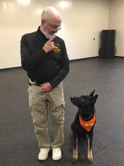 Professor Stephen Mackenzie, head of the university's canine training program, does an obedience drill with his dog Kimo.