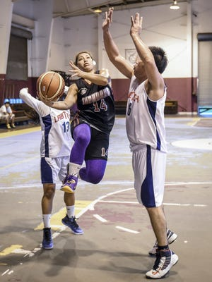 In this 2015 file photo, Tamuning Typhoons' Felicia Borja splits the Lab Tech defense with an up-and-under layup in a Bud Light Golden Hoops Classic Coed Recreation Division playoff game at the Tamuning Gym