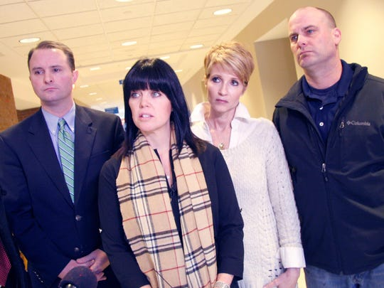 Tracy Stopford, second from left, speaks outside a