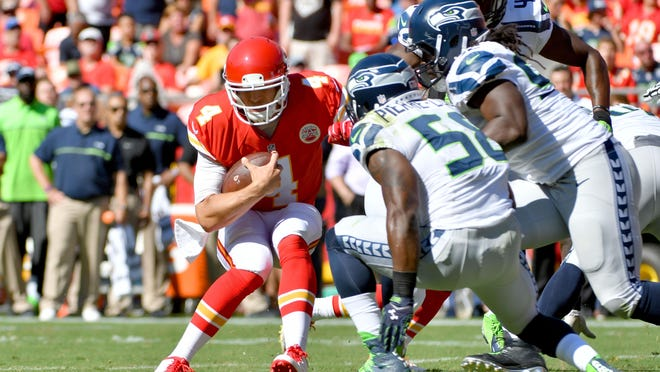 Chiefs quarterback Nick Foles (4) is sacked by Seahawks outside linebacker Kevin Pierre-Louis (58) during the first half at Arrowhead Stadium on Saturday.