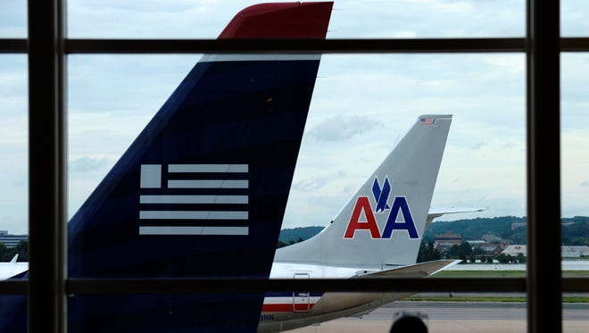 An American Airlines plane and a US Airways plane sit  parked at Washington's Ronald Reagan National Airport in Washington, D.C., on Aug. 13.