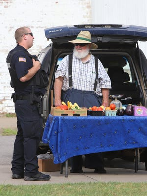 Mansfield police officer Devan Nichols visits with Howard Robinson at the Mansfield Craft Fair, Saturday, July 25, 2020, in the city center. Hosted by Bobbie's Body Care, vendors offered homemade, homegrown and handcrafted items for sale.
