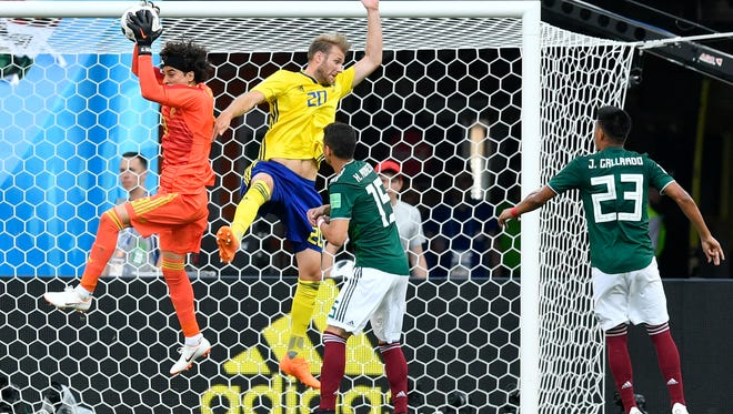 Mexico goalkeeper Guillermo Ochoa, left, jumps for the ball ahead of Sweden's Ola Toivonen, second left, during the group F match between Mexico and Sweden, at the 2018 soccer World Cup in the Yekaterinburg Arena in Yekaterinburg , Russia, Wednesday, June 27, 2018. (AP Photo/Martin Meissner)