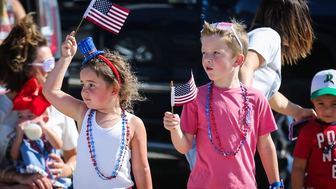 Children get their flags ready for the Fourth of July parade Wednesday, July 4, 2018, in Wall.