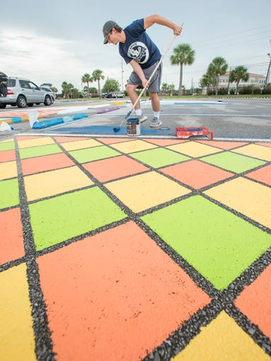 Senior Jordan Pliska paints his parking spot at Gulf