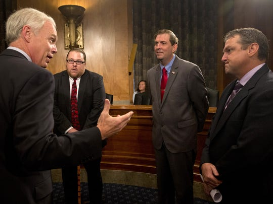"""Senate Homeland Security and Governmental Affairs Committee Chairman Sen. Ron Johnson, R-Wis., left, talks with, from second from left,  Dr. Brandon Coleman, a Phoenix VA Health Care System Addiction Therapist; Joseph Colon, of San Juan, Puerto Rico with the VA Caribbean Healthcare System Credentialing Program Support, and Shea Wilkes, of Shreveport, La., a licensed clinical social worker at the Overton Brooks VA Medical Center, on Capitol Hill in Washington, Tuesday, Sept. 22, 2015, prior to the committee's hearing: """"Improving VA Accountability: Examining First-Hand Accounts of Department of Veterans Affairs Whistleblowers."""""""