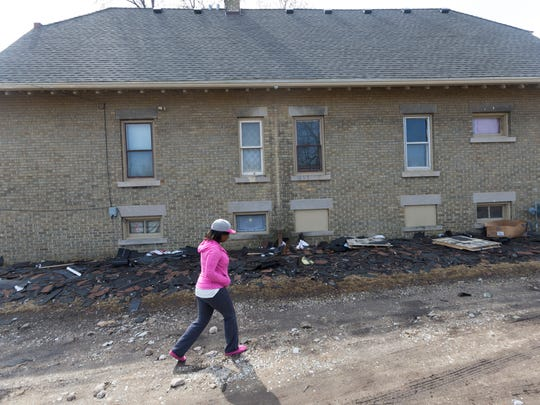 Destinie Grafton walks past old shingles outside the home she rents Wednesday, March 28, 2018 in Milwaukee, Wis. She says notorious landlord Elijah Mohammad Rashaed tried to pressure her into buying the house she rents from him.