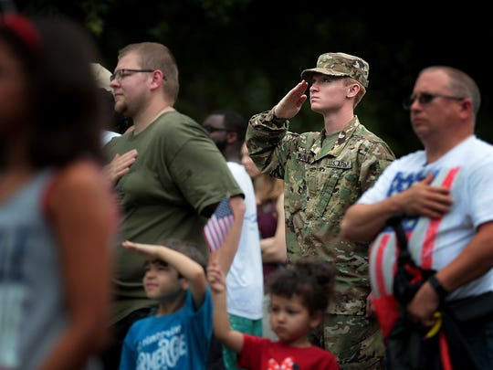 Mitchell Wisdom with the Army National Guard salutes during the national anthem before the start of the Cordova Community Center's Annual Independence Day Celebration and Parade. Memphis Mayor Jim Strickland was the grand marshal of this year's program as community members braved the threatening rain.