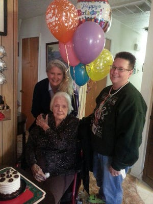 """Evangeline Moorehead Catchpole, center, celebrates her 103rd birthday on Dec. 16 with, at left, Cheryl Choman, director of Partners Assisted Living Services, and Cammie Mobley, the home health care service's client care coordinator. Catchpole was born on Dec. 17, 1913, in Ardmore, Okla. She moved to Pagosa Springs, Colo., and married Harvey Catchpole in 1938, according to information provided by PALS. The couple raised their family and worked in Pagosa Springs until 1990, when Catchpole relocated to Bloomfield to be near her son and daughter-in-law, Harvey and Marka Catchpole. Catchpole, who lives in her home with assistance from PALS caregivers, taught piano lessons throughout her adult life and still plays today. She said the secret to a long life is """"have a happy disposition."""""""