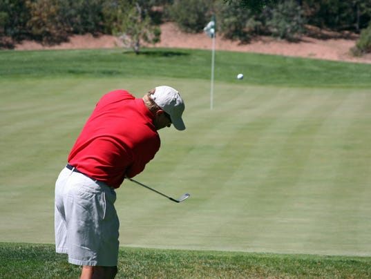 Man chipping ball onto green, focus on golfer