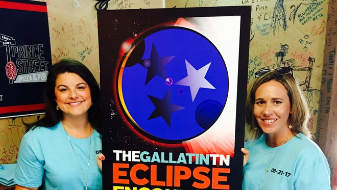 Kim Baker, CEO of the Gallatin Area Chamber of Commerce, (left), and Tracy Sayles with the Sumner County Convention and Visitors Bureau, stand next to Gallatin's Eclipse Encounter poster that was unveiled during a launch party at Prince Street Pizza and Pub on Sunday, Aug. 21, 2016.