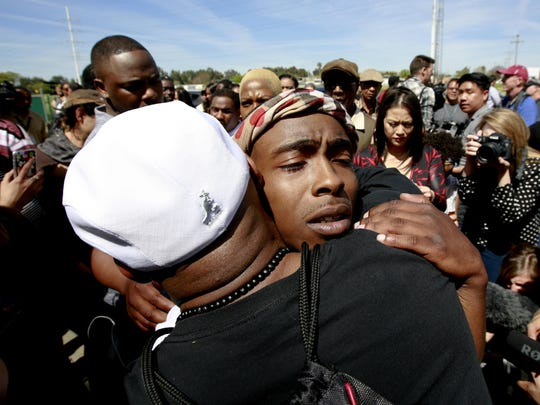 Stevante Clark, the brother of police shooting victim, Stephon Clark, is hugged by a supporter after Stephon Clark's funeral March 29, 2018, in Sacramento, Calif. Stephon Clark who was unarmed, was shot and killed by Sacramento Police Officers, March 18, 2018.