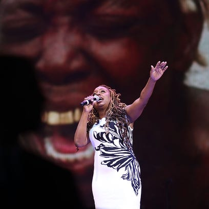 Musician Ledisi sings in front of images projected