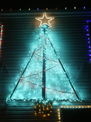 A homemade Christmas tree and star adorn the side of the Parze family house, in Freehold Township.