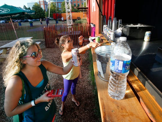 Jessica Micchelli (left) and Stephanie Hanna, both of Wilmington, pick up drinks after a yoga class at Constitution Yards Beer Garden at the Wilmington Riverfront in 2016.