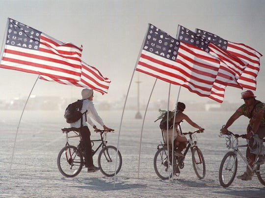 Burning Man participants ride through a group of flags, part of an art installation on the playa north of Gerlach, Nev., Sunday, Aug. 25, 2002. The flags contain symbols of American corporations instead of stars.