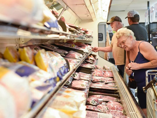 Sharon Saunders looks for good prices on meat at King Saver during its grand opening on Thursday morning. King Saver is located at 725 Richmond Ave., site of the former Community Market.