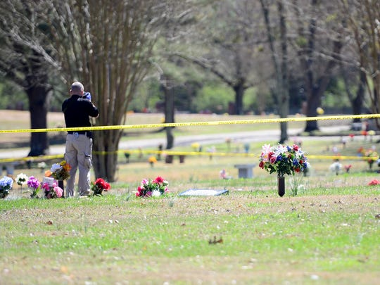 Jackson police investigator photographs the scene of an officer-involved shooting at Ridgecrest Cemetery, Satruday afteroon.