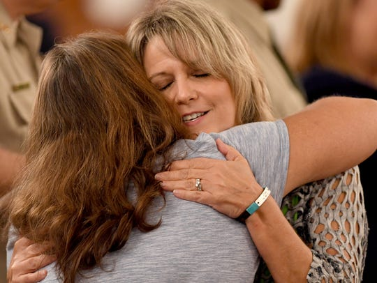 Karen Bobo receives a hug from a supporter after the