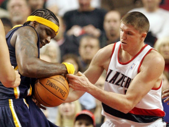 Pacers' Jermaine O'Neal, left, pulls a rebound from