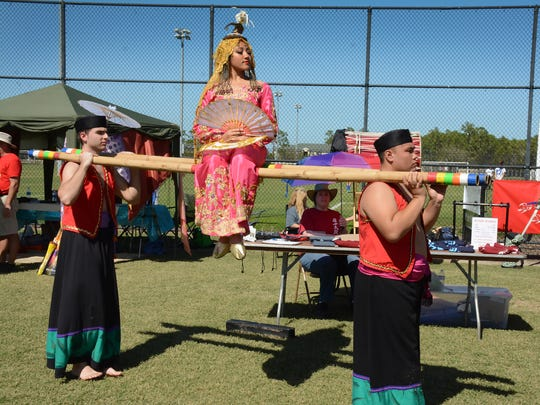 Kristina Biglete is carried atop bamboo poles to perform in a Filipino folk dance at Asia Fest this past weekend.