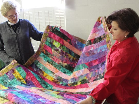 Karen Boyd, left, and Sarah Shelby unfold a colorful quilt before the start of a worknight at Episcopal Church of the Heavenly Rest.