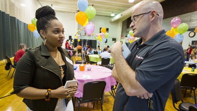 Syretha Shirley (left), a Pike High School graduate, talks with Eric Howard, founder and CEO of Outreach, during the graduation event Saturday, June 14, 2014, at Post Road Christian Church. Shirley will be attending Indiana State University on a scholarship. The students received mentoring and support through Outreach, an Indianapolis nonprofit that reaches out to homeless teens and young adults.