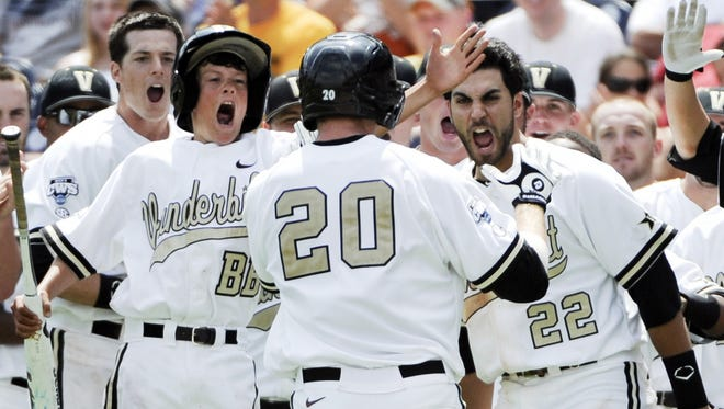 Vanderbilt players, including Jason Esposito (22), greet Connor Harrell (20), after he hit a two-run home run against North Carolina in the sixth inning of an NCAA College World Series baseball game in Omaha, Neb., Saturday, June 18, 2011. (AP Photo/Eric Francis)