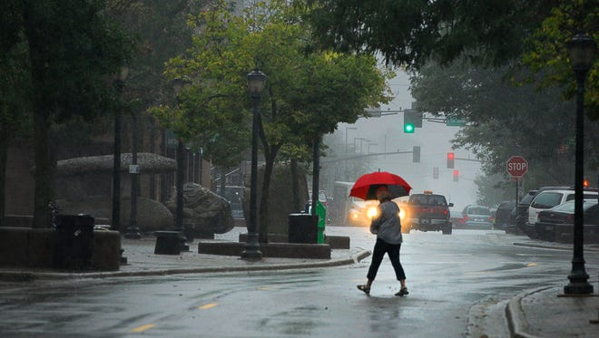 A pedestrian on St. German Street broke out her umbrella to contend with the wind and showers Wednesday.