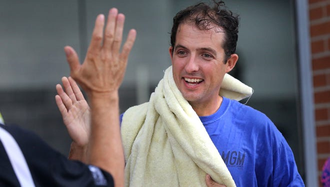 Murfreesboro Mayor Shane McFarland, dries off as he gets a high five from Parks and Recreation Director Lanny Goodwin after they both took the ice bucket challenge at the Murfreesboro Fire & Rescue Station on  Vine Street , on Wednesday August  20, 2014, to raise money for ALS.