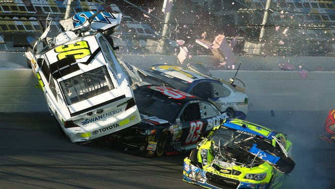 Parker Kligerman (30) gets airborne as he is involved in a crash with Ryan Truex (83), Paul Menard (27), and Dave Blaney (77) during practice Wednesday for the Daytona 500.