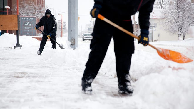 Brian Joshua, 45, back, shovels snow with Carlos Fordham, 18, on Jan. 5 in front of a church in Saginaw, Mich.