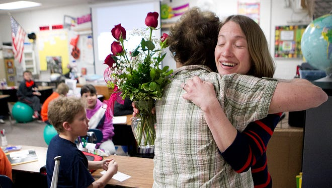 Fourth-grade teacher Lea Hanke, right, receives a hug from fellow teacher Kathy Brunette after being notified that she was a Crystal Apple Award winner in her classroom at Lincoln Elementary School Tuesday, May 6, 2014.