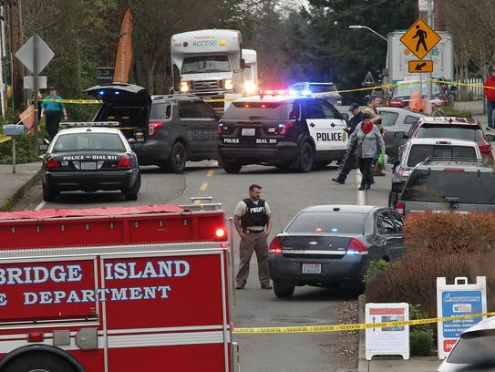 Law enforcement officers investigate the scene of a shooting on Winslow Way on Bainbridge Island on Wednesday.