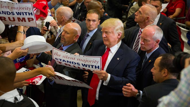 Presidential candidate Donald Trump signs items handed to him by supporters during a rally at the Albuquerque Convention Center, May 24, 2016.