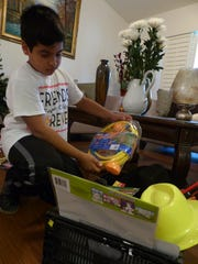 Leonardo Iriarte, 10, goes through the recent toy donations he received from people in the community for foster children.