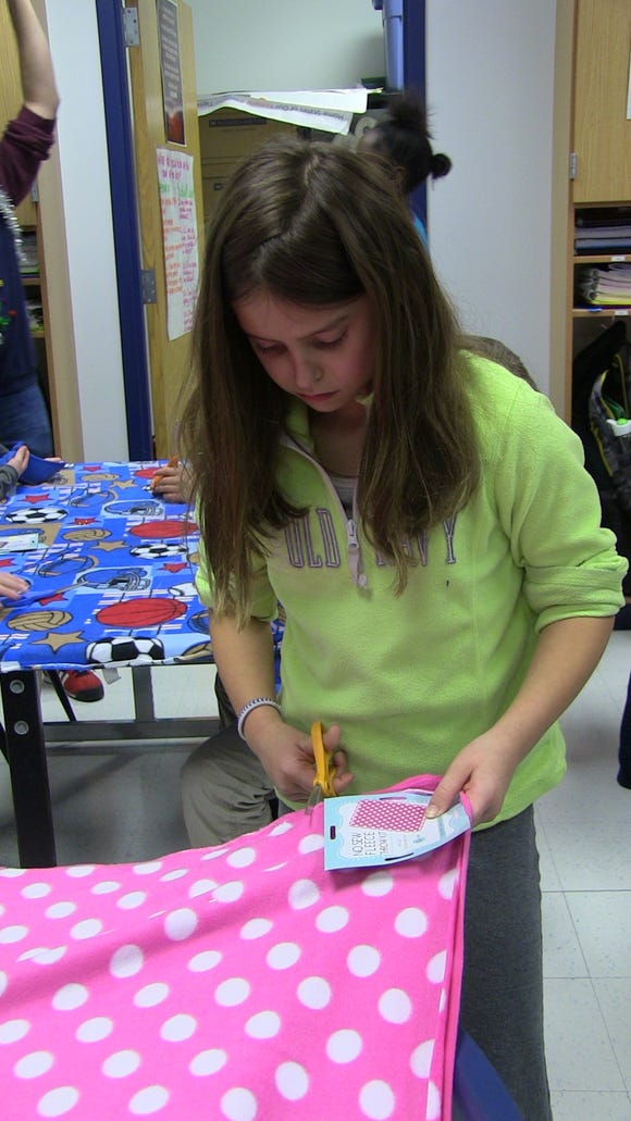 Fifth grader Amelia Ochsner cuts fleece to make a blanket for a family at the Ronald McDonald House.