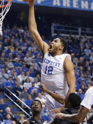 Kentucky's Karl-Anthony Towns (12) dunks between Missouri's Namon Wright, left, and Wes Clark during the first half of an NCAA college basketball game in Lexington, Ky., Tuesday, Jan. 13, 2015. (AP Photo/James Crisp)