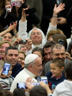 Pope Francis is cheered by faithful during an audience with the Holy See's employees at the Vatican on Dec. 22, 2014.
