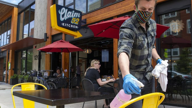 Adam Vernon wipes down a table at Claim 52 in the sidewalk space allowed under a new permit system program by the city of Eugene enabling businesses to expand their serving space into the public right of way and parking spaces. The city created the pilot program last week with the goal of increasing capacity at local restaurants while accommodating safe physical distancing. [Andy Nelson/The Register-Guard] - registerguard.com