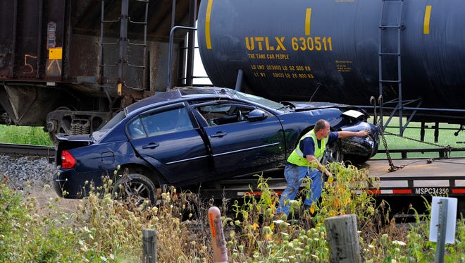 A car is towed out of a ditch near the tracks after a fatal car/train accident on N. Cochran near M-43 in Eaton County's Oneida Township Thursday August 19, 2015.