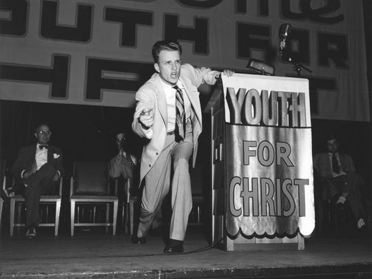 A young Billy Graham preaches at a youth crusade. Location unknown.