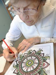 Janice Wolowicz works on her coloring sheet during