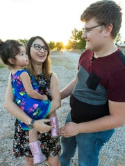 Luz Skywalker, 21, Zach Eason, 20, and their daughter Luna, 2, go for a walk near Zach's home on Tuesday. Zach and Luz are engaged to be married.