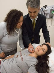 Dr. Kamran Kamali, a professor of surgery at Burrell College of Osteopathic Medicine, shows medical student Julie Obregon, left, where to find a pulse on Bianka Martinez, lying down, during a demonstration of teaching techniques used at the school.