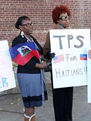 Berthilde Dufrene, founder of Haitian American Nurses Association of Rockland County, and member Ernsta Pierre attend a rally to call on President Trump to reconsider ending immigration protections early Nov. 21, 2017 at Fireman Kevin Landau Park in New City
