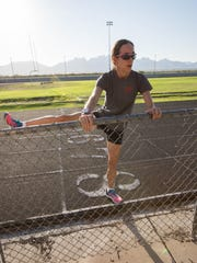 Lucinda Hemingway, a member of the Las Cruces SunDragons Athletics Track and Field Club, stretches before her morning run at Oñate High School's track on Monday, Aug. 6.