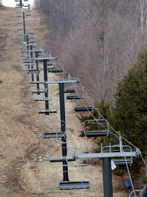A chairlift sits idle at Oak Mountain Ski Center on Tuesday, Dec. 8, 2015, in Speculator, N.Y. Some Northeasterners are beginning to wonder if a white Christmas may just be a dream, and business owners who rely on snow are starting to worry if warm weather could lead to a nightmare winter.