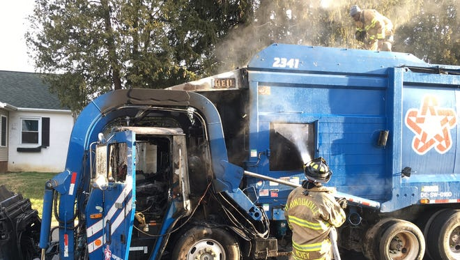 Firefighters from the Minquadale Fire Company work on extinguishing a garbage truck fire.